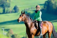 Caballo de montar a caballo de la mujer Fotografía de archivo libre de regalías