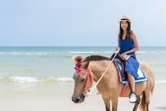 Caballo de montar a caballo de la mujer en la playa de la arena Foto de archivo