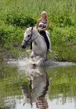 Caballo de montar a caballo de la mujer por el lago rural Imágenes de archivo libres de regalías