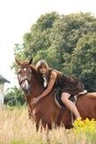 Caballo de montar a caballo hermoso de la muchacha del adolescente en el campo de flores Foto de archivo