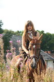 Caballo de montar a caballo hermoso de la muchacha del adolescente en el campo de flores Imagen de archivo libre de regalías