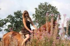 Caballo de montar a caballo hermoso de la muchacha del adolescente en el campo de flores Fotografía de archivo