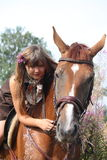 Caballo de montar a caballo hermoso de la muchacha del adolescente en el campo de flores Imágenes de archivo libres de regalías