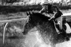 Caballo de montar a caballo a través del agua en el evento de tres días