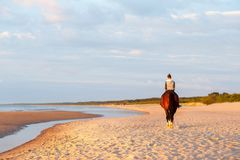 Caballo de montar a caballo del adolescente en la playa en la puesta del sol outdoors Imagen de archivo libre de regalías