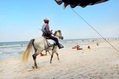 Caballo de montar a caballo del viejo hombre a la playa arenosa en el cha  imagen de archivo libre de regalías