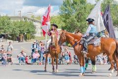 Caballo de montar a caballo de la muchacha y bandera canadiense de la tenencia en el desfile fotografía de archivo