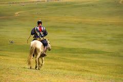 Caballo de montar a caballo tradicional del hombre mongol cuesta abajo fotografía de archivo libre de regalías