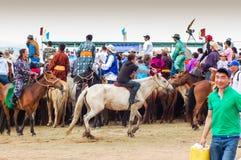 A caballo espectadores que miran la carrera de caballos de Nadaam Imagen de archivo libre de regalías
