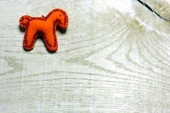 Caballo hecho a mano del fieltro adornado con las gotas en fondo de madera Fotografía de archivo libre de regalías