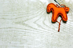 Caballo hecho a mano del fieltro adornado con las gotas en fondo de madera Fotos de archivo