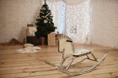 Caballo mecedora de madera adentro adornado por la Navidad al sitio Foto de archivo libre de regalías