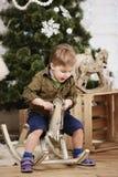 Caballo mecedora de madera del pequeño paseo del muchacho delante del árbol de navidad Imagen de archivo libre de regalías