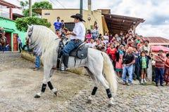 A caballo paseos del vaquero en el pueblo, Guatemala Foto de archivo