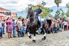 A caballo paseos del vaquero en el pueblo, Guatemala Foto de archivo libre de regalías