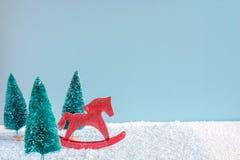 Caballo retro del juguete de la Navidad con los árboles de pino en la tabla de madera cubierta con nieve Foto de archivo libre de regalías