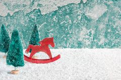 Caballo retro del juguete de la Navidad con los abetos en la tabla de madera cubierta con nieve sobre fondo de la pared del grung Imágenes de archivo libres de regalías