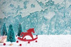 Caballo retro del juguete de la Navidad con los abetos, las bayas rojas y la caja de regalo en la tabla de madera cubierta con ni Fotos de archivo libres de regalías