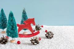 Caballo retro del juguete de la Navidad con los abetos, las bayas rojas y los conos del pino en la tabla de madera cubierta con n Foto de archivo
