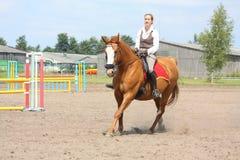 Caballo rubio joven hermoso de la castaña del montar a caballo de la mujer Imágenes de archivo libres de regalías