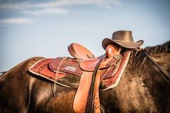 Caballo y silla de montar con el vaquero Hat fotos de archivo