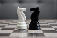 Caballos blancos y negros del ajedrez delante de uno a como concepto del desafío y de la competencia imagenes de archivo