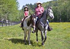 Caballos de montar a caballo de la muchacha y de la mujer Fotografía de archivo libre de regalías