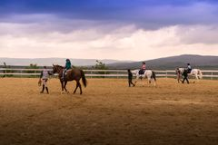 Caballos de montar a caballo en la arena con los instructores y los niños imagenes de archivo