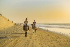Caballos de montar a caballo jovenes de los pares en la playa Foto de archivo