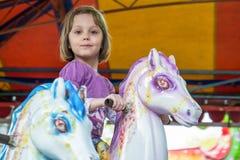 Caballos del carrusel del montar a caballo de la chica joven Imagen de archivo libre de regalías