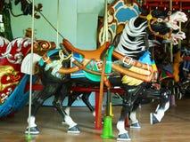 Caballos en un carrusel tradicional del parque de atracciones Imágenes de archivo libres de regalías