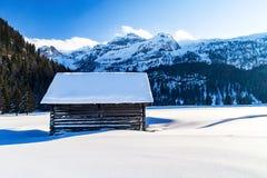 Cabana da montanha só em paisagem arrebatadora da neve foto de stock