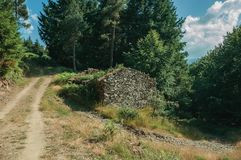 Cabana de pedra na bifurcação de uma estrada de terra em um bosque fotografia de stock