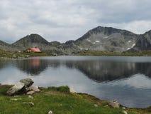 Cabana do turista pelo lago da montanha Fotos de Stock Royalty Free