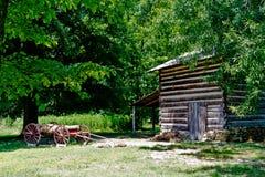 Cabana rústica de madeira com o vagão no parque da Hagan-pedra Fotografia de Stock Royalty Free