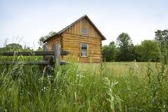 A cabana rústica de madeira dos colonos adiantados na pradaria imagem de stock