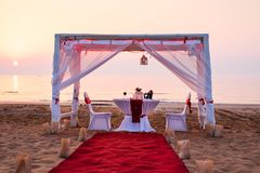 Cabana and romantic dinner setting on a beach. At sunset, candle, chair, table, private, hanging, date, water, sea, tropical, decoration, coast, exotic, two royalty free stock photos