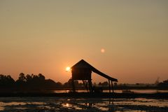 Cabanas asiáticas do sudeste do pantanal da silhueta do luminoso da foto imagens de stock royalty free