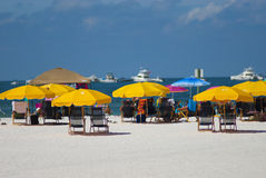 Cabanas on beach. Clearwater beach with yellow cabanas and boats anchored in the ocean watching the boats race Royalty Free Stock Photography