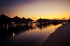 Cabanas tropicais ao longo de uma praia no por do sol fotos de stock