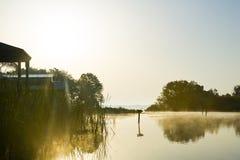 Cabanes silhouettées au lever de soleil sur le lac Panasoffkee images libres de droits