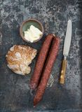Cabanossi lunch. Cabanossi sausages with bread and butter on rustic table Royalty Free Stock Images