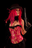 Cabaret girl in pink corset holding gun. Isolated on black background stock photo