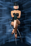 Cabaret showgirl on bar chair. Cabaret showgirl is sitting on bar chair against an abstract background Stock Images