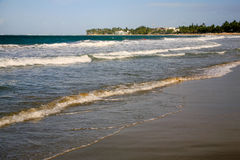 Cabarete Bay, Cabarete, Dominican Republic. Gentle waves are breaking on the beach at Cabarete, Dominican Republic. Hotels and villas are in the background Stock Photo
