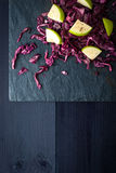 Cabbage and apples salad on the dark stone Royalty Free Stock Images