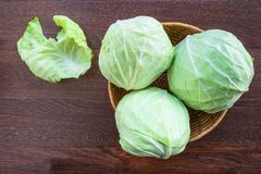 Cabbage in a basket on a wooden table royalty free stock photos