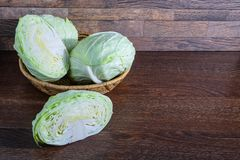 Cabbage in a basket on a wooden table stock photography