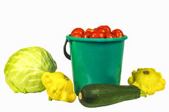 Cabbage, bucket with tomatoes, zucchini and squash on a white ba Royalty Free Stock Photo