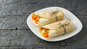 Two vegetable roll tortilla from wheat flour in white bowl on a dark wooden table. Cabbage, carrot, pepper, avocado, tomatoes in pita bread on a rustic table Royalty Free Stock Photo